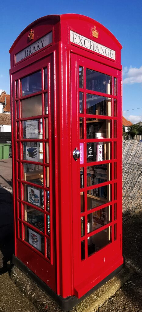 a Local free library book swapping service inside an old red, telephone box once found everywhere in the UK