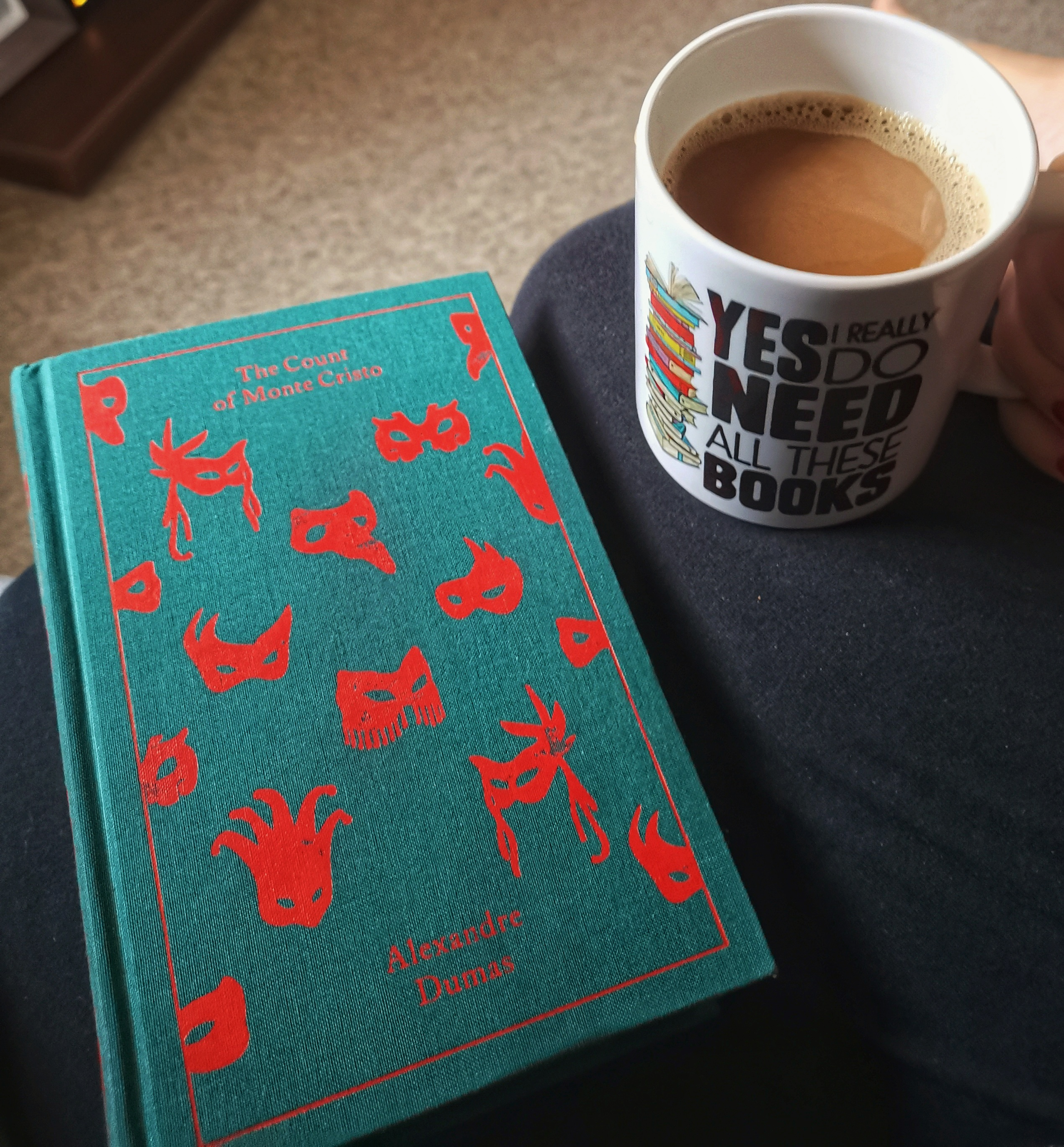 the cloth bound classic The Count of Monte Cristo and a mug of coffee