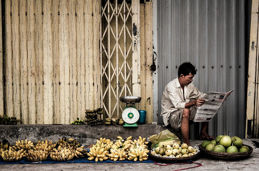 The streets of Vietnam where people sell food and spend the day reading newspapers while waiting for customers.